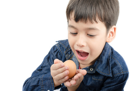 hand in mouth: Little boy holding egg in hand mouth wide healthy on white background