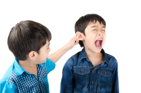 Kleine broer jongen vechten door te trekken oor zijn broer op een witte achtergrond Stockfoto