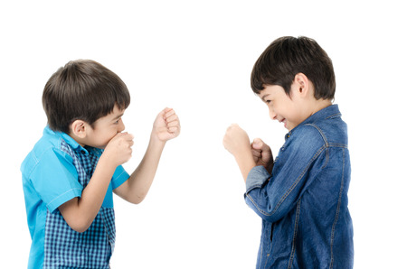 sibling rivalry: Little sibling boy fighting on white background