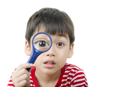 Little boy using magnifier close up on white background photo