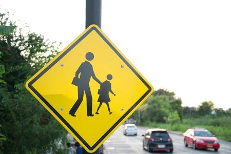 signos de precaucion: Reg�strate cerca de la escuela esperar a chico cruzar la calle con el cielo azul Foto de archivo