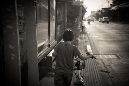 little boy walking with bike on the street photo