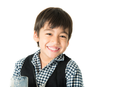 pequeño: El niño pequeño bebe la leche en el fondo blanco; Foto de archivo