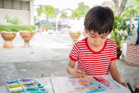 Jongetje tekening beeld op tafel outdoor; Stockfoto