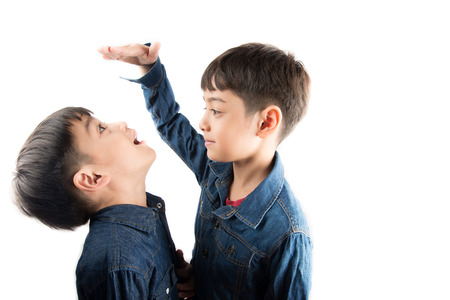 measure height: Little sibling boy brothers checking there tall each other Stock Photo