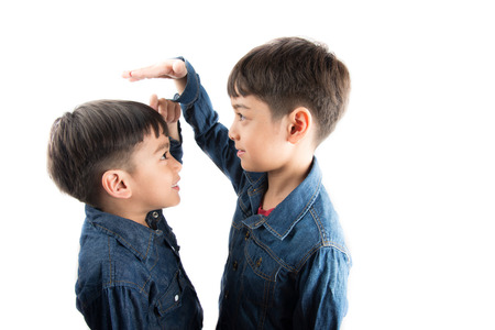 Little sibling boy brothers checking there tall each other Stockfoto