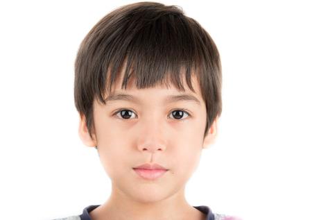Niño pequeño que toma la foto retrato con los ojos hermosos en el fondo blanco