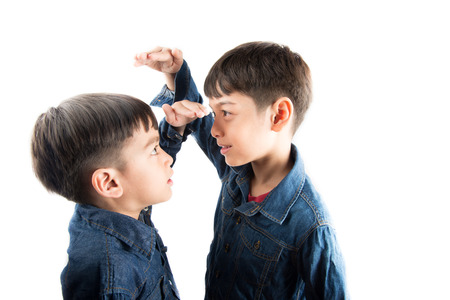 Little sibling boy brothers checking there tall each other Stock Photo