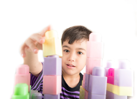 ni�os jugando: Little boy playing blocks at home