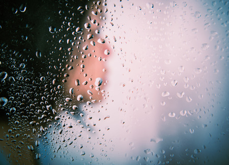 tr: Woman portrait side behind the glass full with water drop Stock Photo
