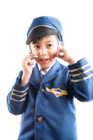 niños sosteniendo un cartel: Niño finge como piloto en el fondo blanco Foto de archivo