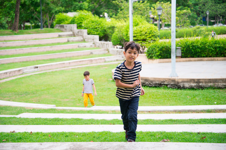 five people: Little boy walking on the step in the park