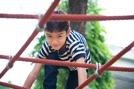 jungle gyms: Little boy climbing rope at plaground