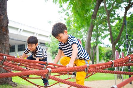Jongetje klimtouw op plaground Stockfoto