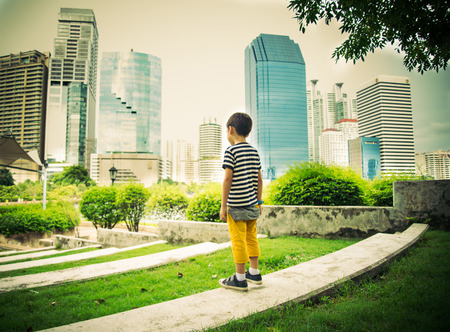 five people: Little boy standing looking in the city park