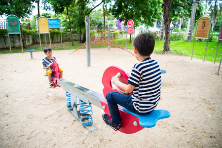 totter: Little boys playing seesaw together in the park Stock Photo
