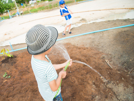 experiential: Little boy working planting in the farm outdoor
