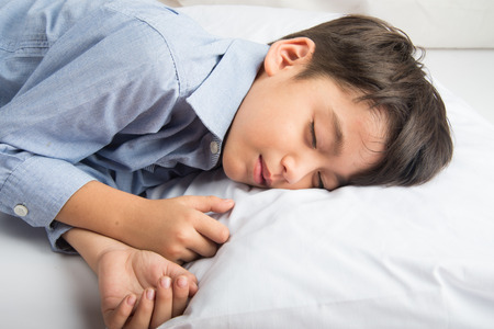 night life: Little boy laying down on the bed cute beautiful face on white background