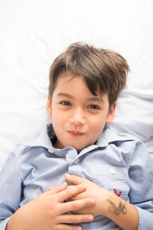 young boy smiling: Little boy laying down on the bed cute beautiful face on white background