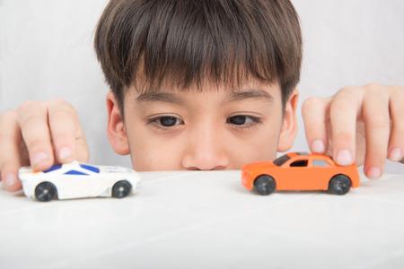 Weinig jongen die met autostuk speelgoed spelen op de lijst Stockfoto