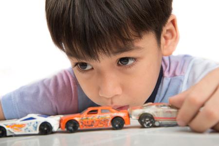 Weinig jongen die met de auto speelgoed op de tafel