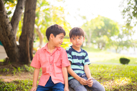 Little sibling boy sitting together in the park