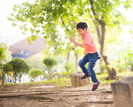 Little boy jumping in the park Imagens
