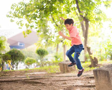 Little boy jumping in the park Standard-Bild