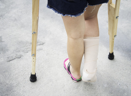 crutches: Close up of hands holding crutches on the street
