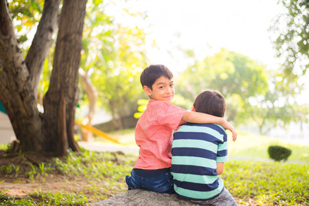 sibling: Little sibling boy sitting together in the park