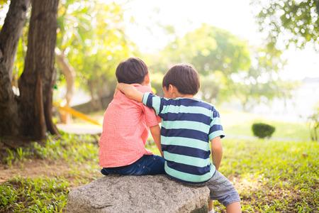 Kleine broer jongen zitten samen in het park Stockfoto