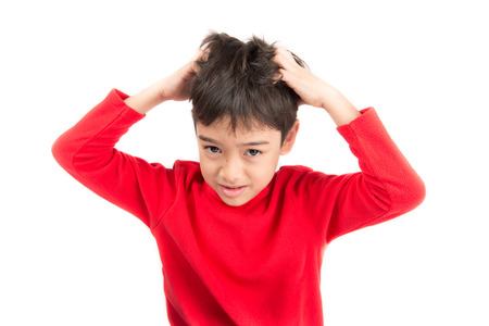 Little boy itchy his hair on white background Archivio Fotografico