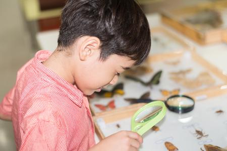 experimento: Niño pequeño aprendiendo clase de ciencias con el microscopio Foto de archivo