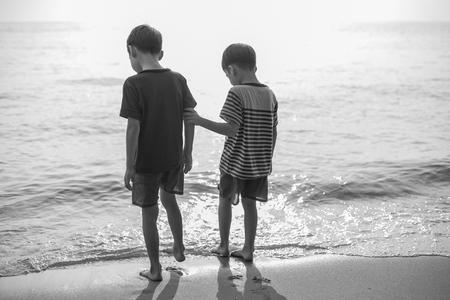 nue plage: Petit fr�re gar�on debout sur la plage ensemble noir et blanc Banque d'images