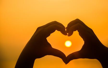 Mano haciendo forma de corazón sobre la puesta del sol Foto de archivo - 48658340
