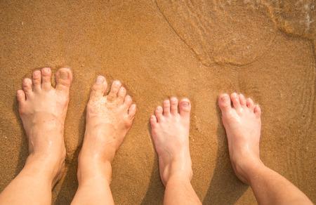 sandalias: Pies de niño de pie por sí sola en la playa de arena