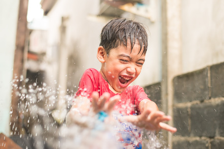 Little boy playing water splash
