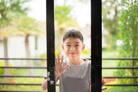 glass door: Little boy opening door in the house Stock Photo