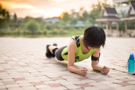 doing: Asian woman work out planking in the park Stock Photo
