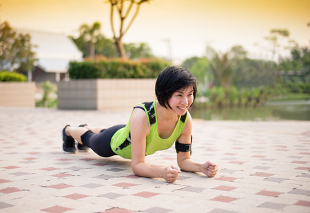 Asian woman work out planking in the park Stock Photo