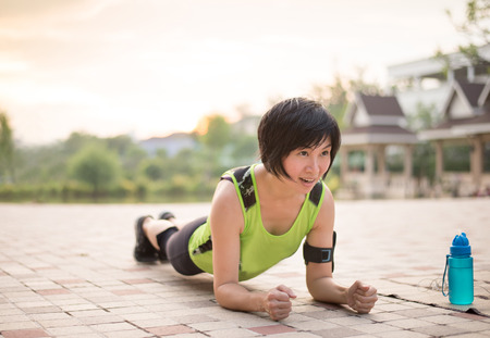 planking: Asian woman work out planking in the park Stock Photo
