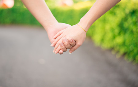 manos entrelazadas: Amantes de la mano que sostiene juntos al caminar Foto de archivo