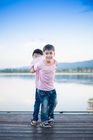 sibling: Little sibling boy standing together nearby lagoon
