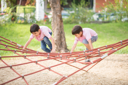 asian youth: Little boy climbing on the rope at playground