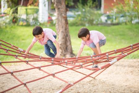 niño escalando: Niño pequeño que sube de la cuerda en el patio