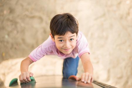 Jongetje climping up moedig bij speelplaats
