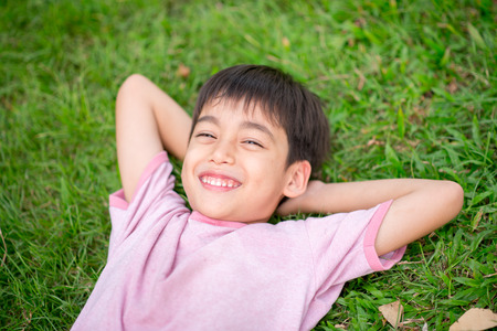 beautiful boy: Little boy lay down on the grass  with smile