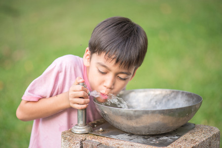 arab spring: Little boy drinking public water in the park Stock Photo