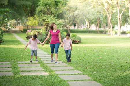 single mother: single mother walking in the park with sons