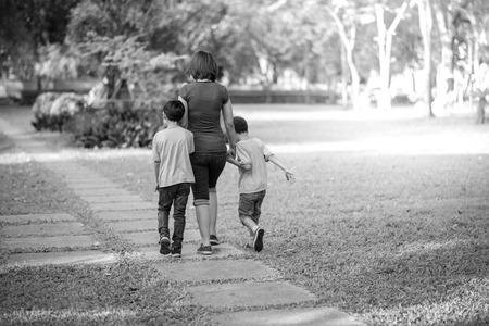 madre soltera: madre soltera caminar en el parque con hijos
